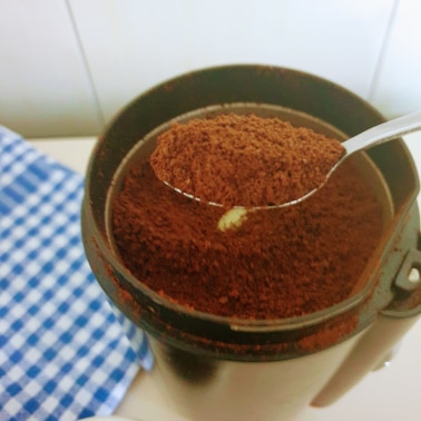 Coffee beans ground to a perfect size for moka pot brewing method in an electric coffee grinder