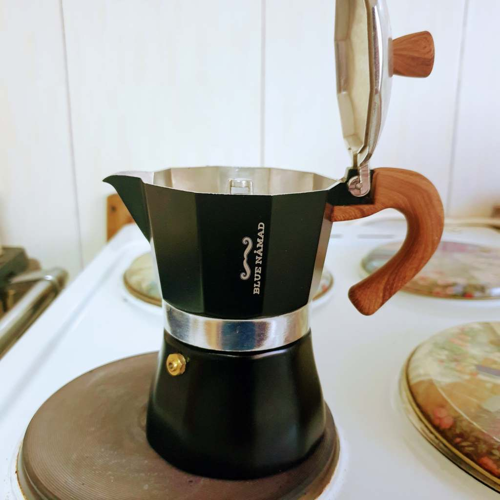 Moka pot filled with water and coffee on an electric stove with the lid open ready for brewing