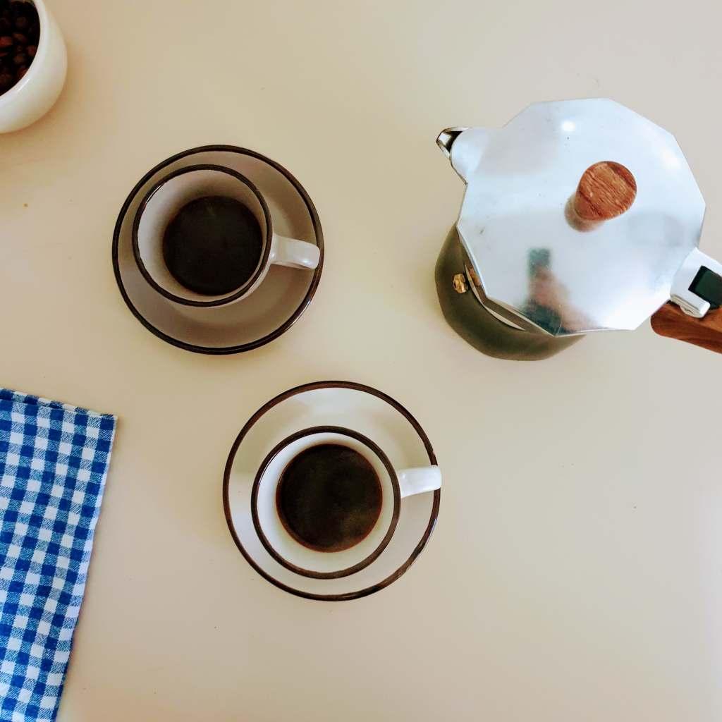 Moka pot and two cups of coffee prepared in the moka pot