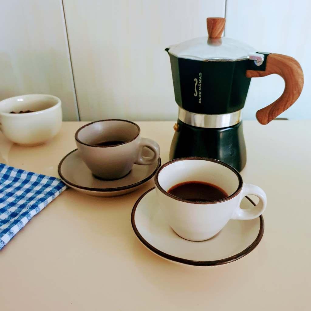 Moka pot and two cups of coffee prepared in the moka pot.
