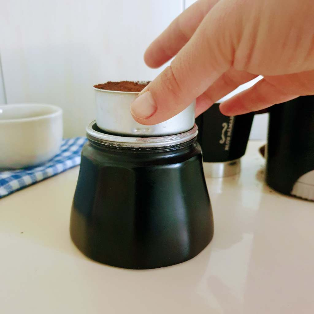 Placing the coffee basket of a moka pot into the lower chamber of the moka pot which is already filled with hot water