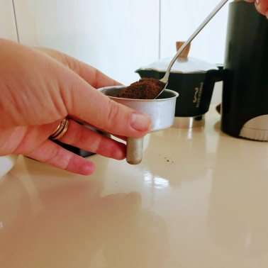 Filling the basket of a moka pot with freshly ground coffee