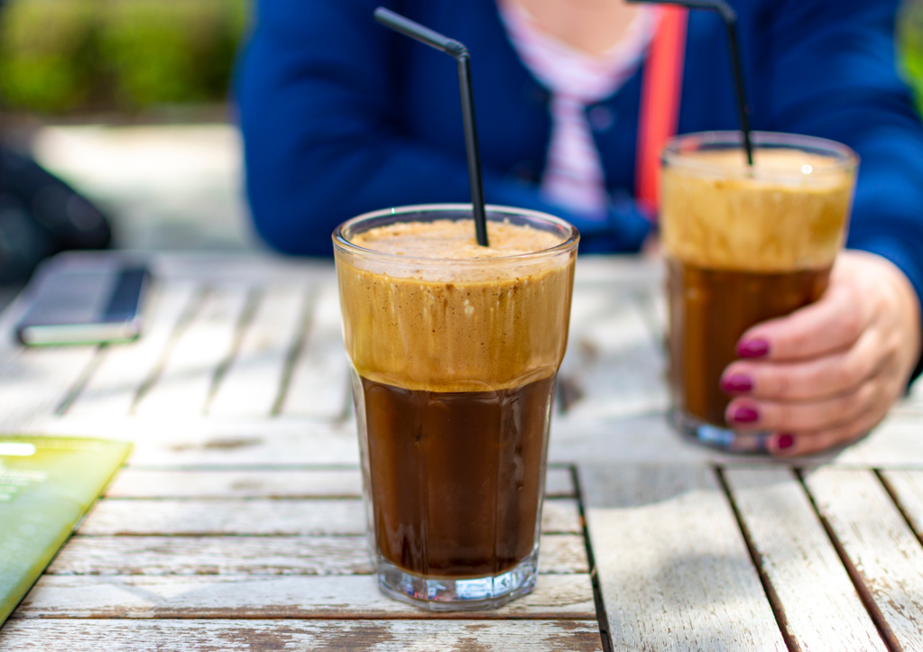 Two glasses with Greek frappe, iced coffee made of instant coffee, water and ice. A woman hand holding one glass of iced coffee.